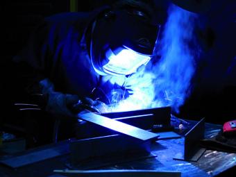 Kovovýroba. Svářeč. Pracovník předkloněný nad svařovací stůl a svařující kovový materiál ve svářecí kukle v malosérii. Kovovýroba na míru.